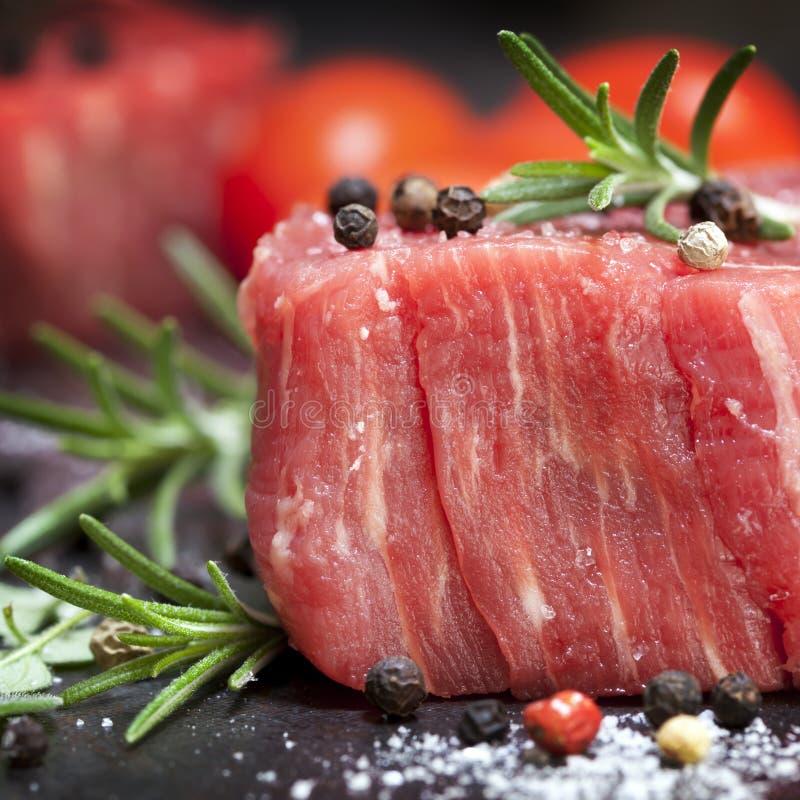 Rohes Steak mit Pfefferkörnern und Kräutern stockfotografie