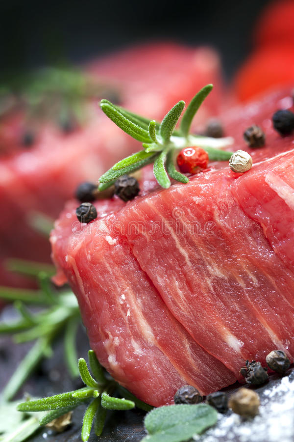 Rohes Steak mit Pfefferkörnern und Kräutern lizenzfreie stockfotografie