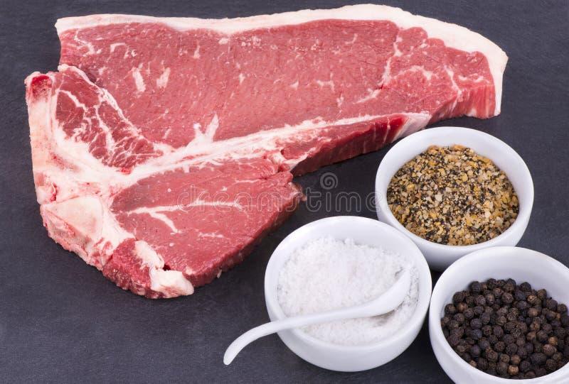 Rohes T-Bone-Steak und Gewürz lizenzfreies stockbild