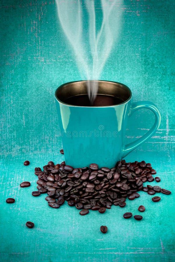 Rohkaffeebecher und Kaffeebohnen stockbild