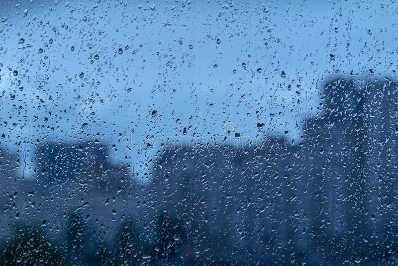 Rohwassertropfenhintergrund auf Glas Unscharfer Stadthintergrund stockfotos