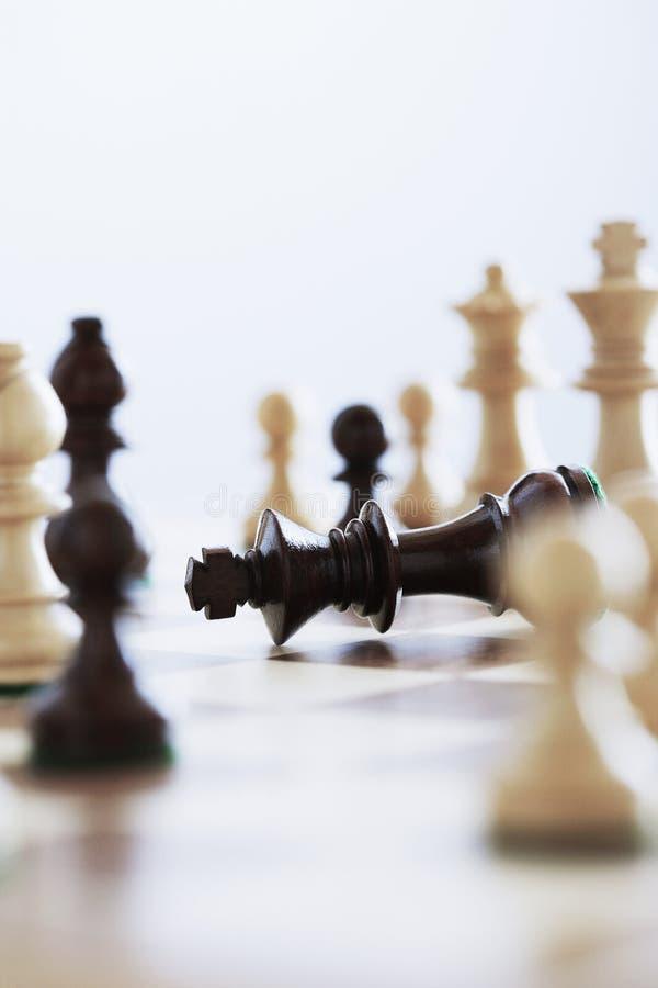 Roi de jeu d'échecs se trouvant à bord entouré par des morceaux photographie stock