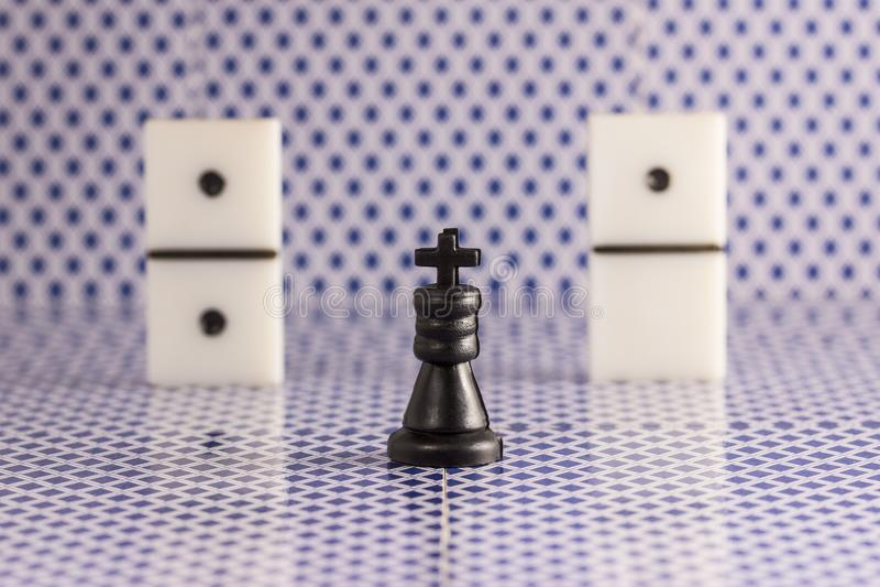 Roi et matrices noirs d'échecs pour des dominos sur un fond brouillé de l'arrière de jouer des cartes images stock
