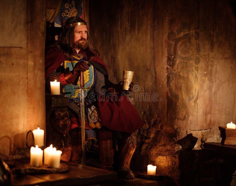 Roi médiéval avec le gobelet de vin sur le trône dans l'intérieur antique de château image libre de droits