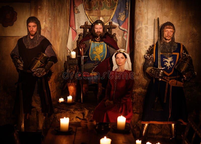 Roi médiéval avec sa reine et chevaliers sur la garde dans l'intérieur antique de château image stock