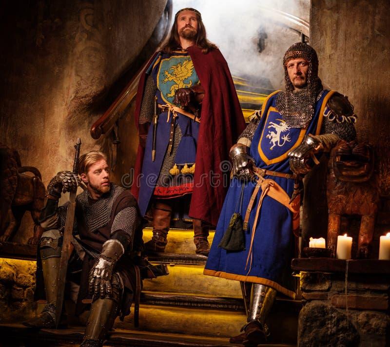 Roi médiéval avec ses chevaliers dans l'intérieur antique de château photos stock
