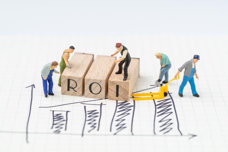 ROI retur på investeringbegreppet, miniatyrfolkstatyetter honom arkivbilder