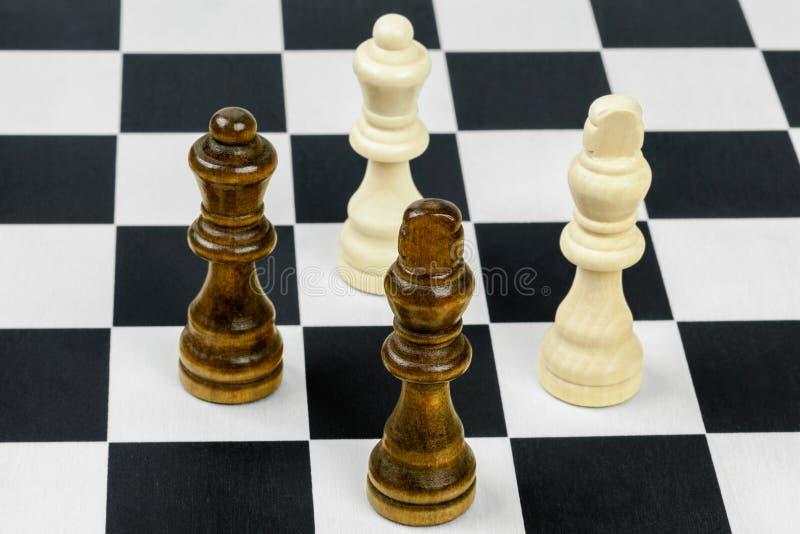 Rois et reines d'échecs sur l'échiquier photographie stock