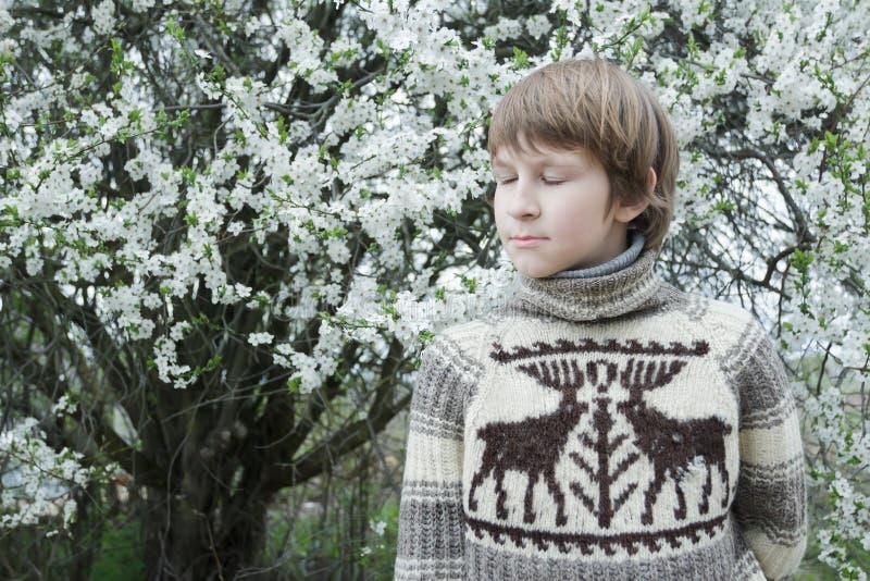 Rojenie nastoletni chłopak z zamknięty oczu być ubranym obraz stock