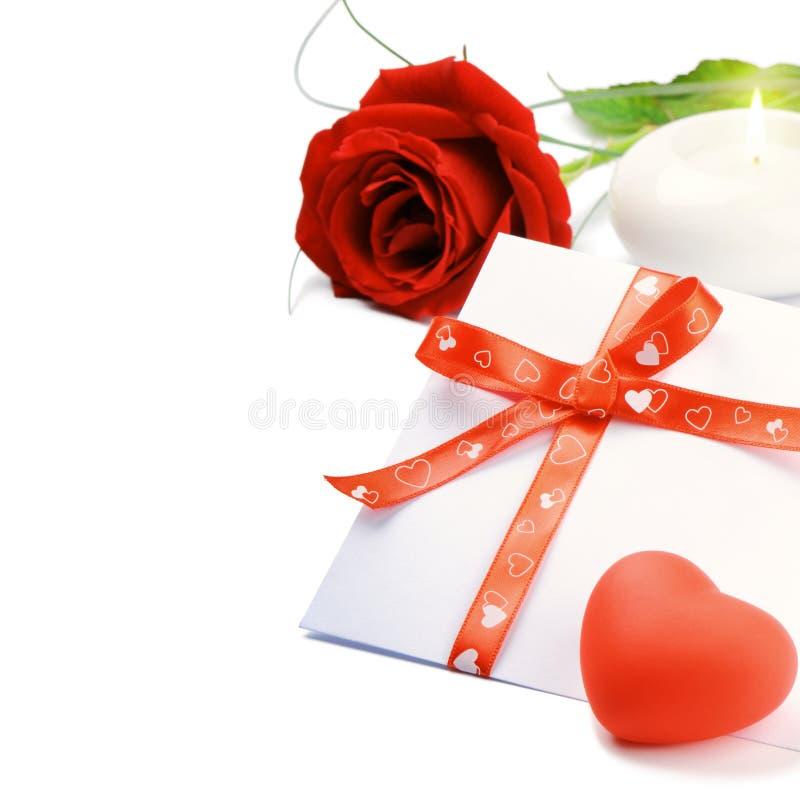 Rojo color de rosa y sobre en conjunto romántico imagen de archivo libre de regalías