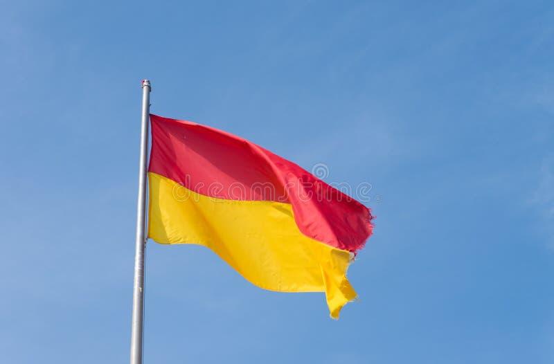 Rojo con la bandera amarilla fotos de archivo