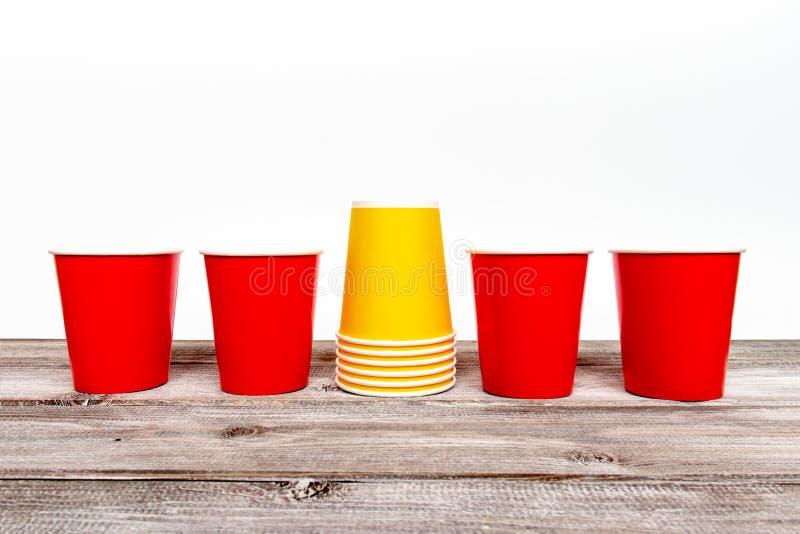 Rojo cuatro y pila de tazas disponibles de papel amarillas para el café y de bebidas sin alcohol en fondo de madera foto de archivo
