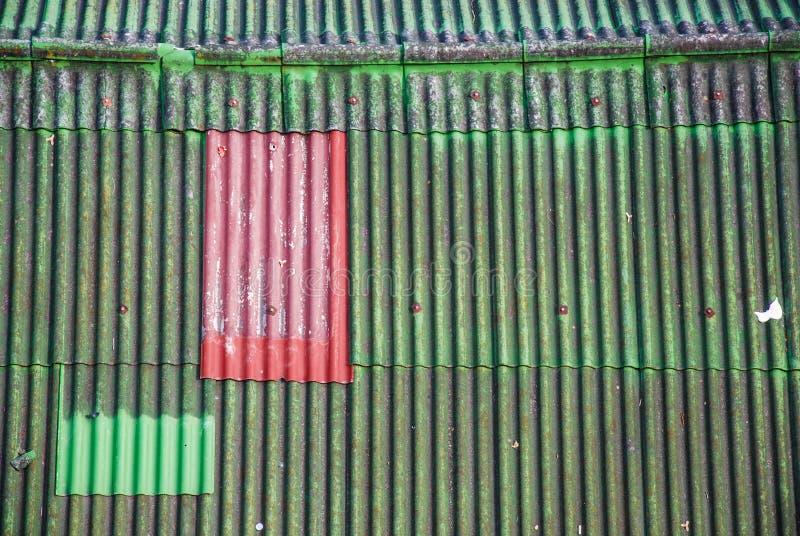Rojo en tejado verde imagenes de archivo