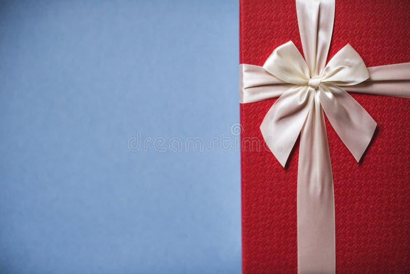 Rojo lleno presente con el arco en fondo azul fotografía de archivo libre de regalías