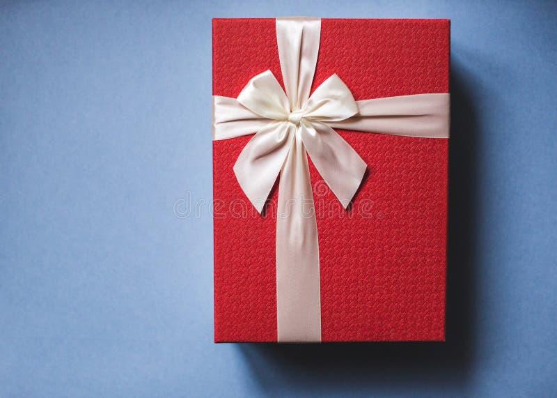 Rojo lleno presente con el arco en fondo azul imágenes de archivo libres de regalías