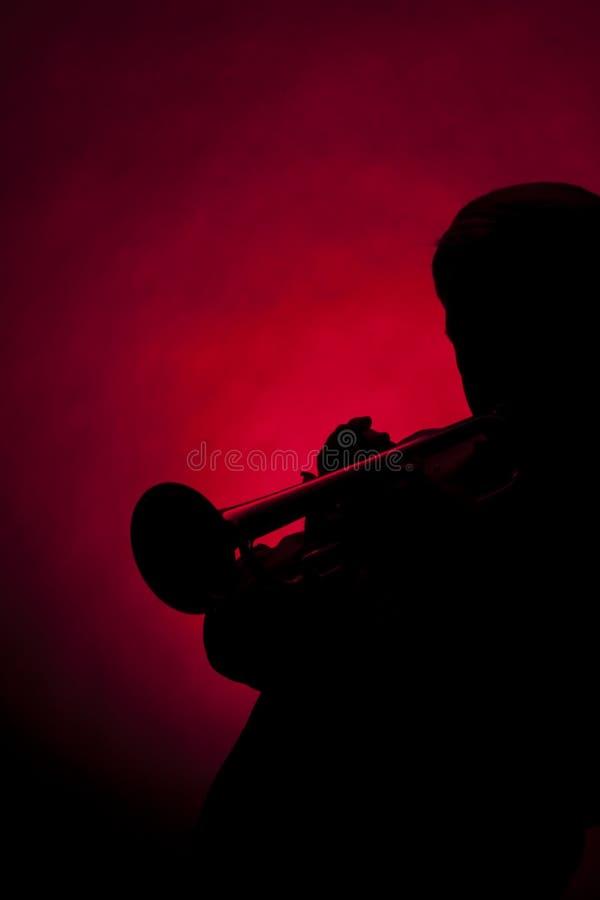 Rojo masculino mayor de la silueta del jugador de la trompeta fotos de archivo