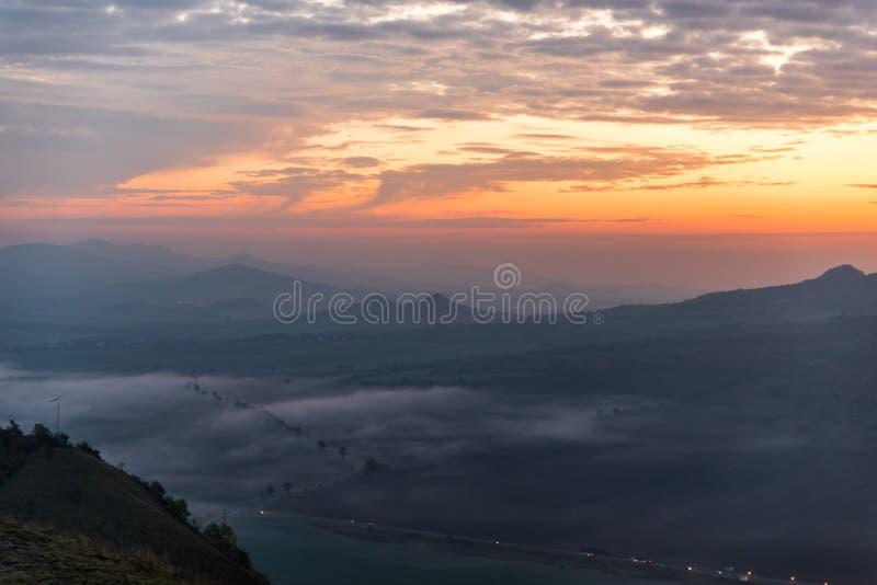 Rojo, oragne y salida del sol dinámica azul con la niebla que pone en valle fotografía de archivo libre de regalías