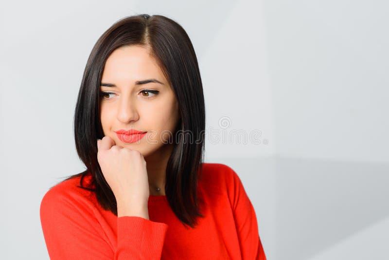Rojo que lleva sonriente pensativo moreno de la mujer joven fotografía de archivo libre de regalías