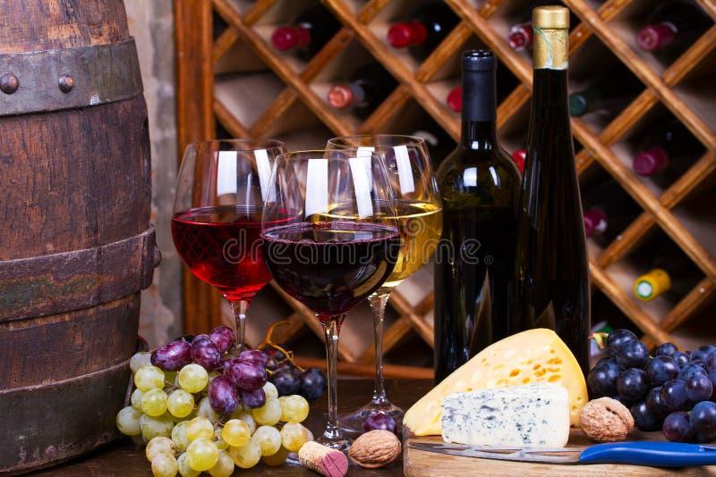 Rojo, vidrios color de rosa y blancos y botellas de vino foto de archivo