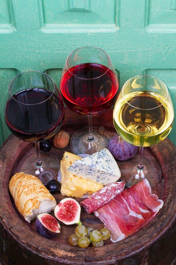 Rojo, vidrios color de rosa y blancos y botellas de vino Queso, higo, uva, prosciutto y pan en barril de madera viejo foto de archivo
