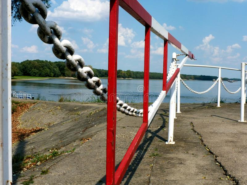 rojo y blanco con la cadena pesada y la puerta en perspectiva de disminución en un lado del río fotografía de archivo libre de regalías