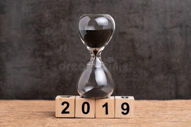 Rok 2019 czasów odliczanie, czasu przelotny pojęcie, hourglass lub sandglass na sześcianu drewnianym blokowym budynku liczba 2019 zdjęcie royalty free