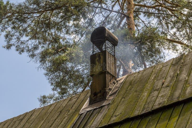 Rokend schoorsteen houten dak royalty-vrije stock foto's