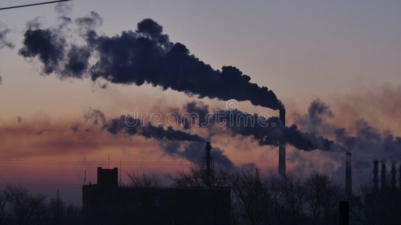 Rokende fabrieksschoorstenen Milieuprobleem van verontreiniging van milieu en lucht in grote steden Mening van grote installatie royalty-vrije stock foto
