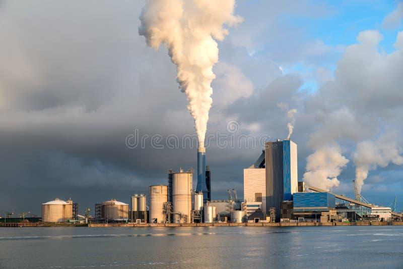 Rokende schoorsteen bij zonsondergang op industriële complexe gebouwen stock foto