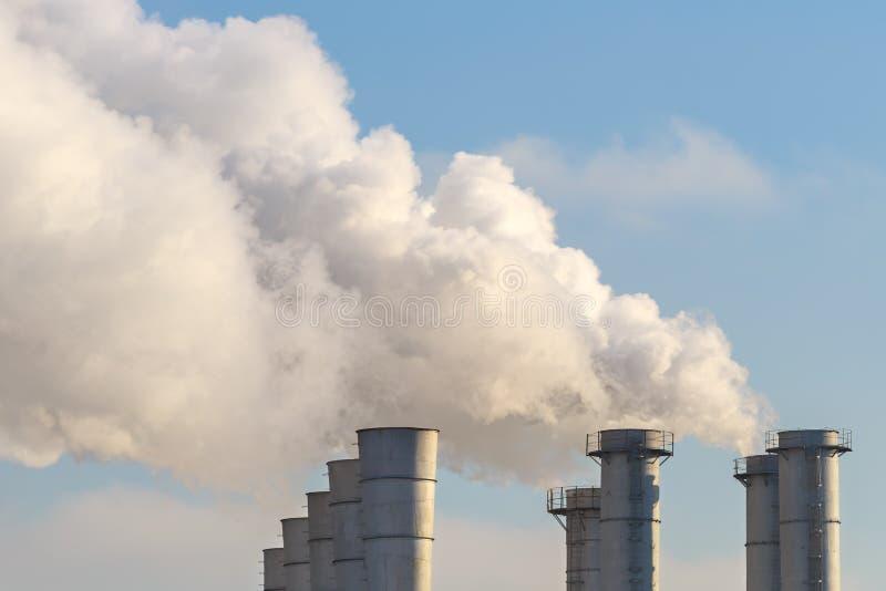 Rokende schoorstenen op achtergrond van de blauwe hemel als illustratie van de verontreiniging van aard en een disbalance van de  stock afbeelding