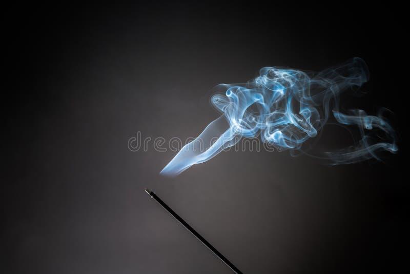 Rokende wierookstok met rook het uitgaan op Zwarte Achtergrond Zuiver ontspanningsthema, rookstoom, rookgolven, mist en mist stock foto