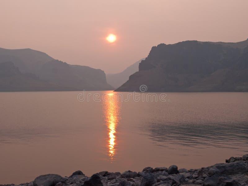 Rokerige zonsondergang bij bergmeer   royalty-vrije stock fotografie