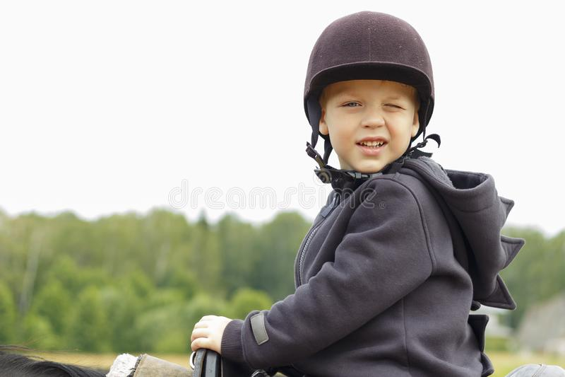 3 roku chłopiec sadzającej na horseback w hełmie, uczy się jechać zdjęcia stock