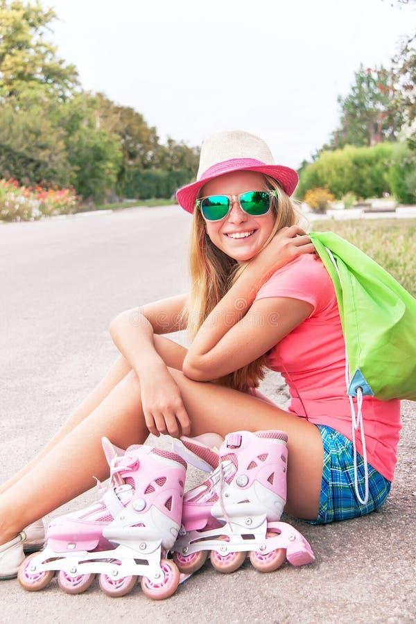 Rol het schaatsen tiener (meisje) zitting met rol het schaatsen schoenen royalty-vrije stock foto