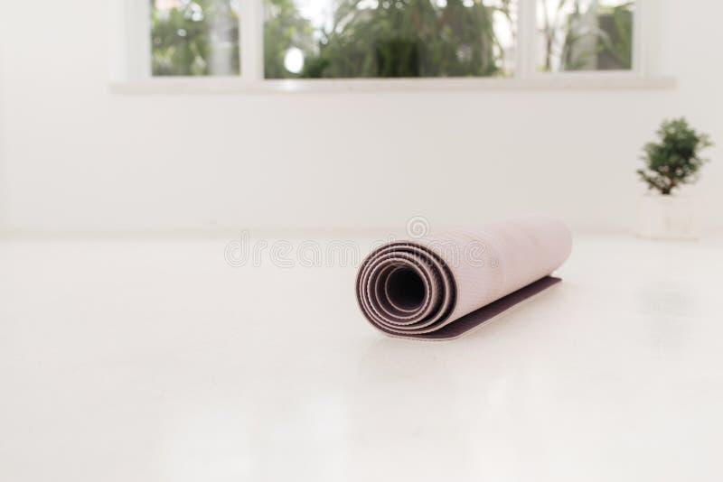 Rolado acima da esteira da ioga ou dos pilates para o exercício no assoalho de madeira natural, classe do esporte antes ou depois foto de stock