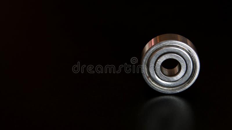 Rolamento de esferas de Chrome no preto, parte da peça do mecanismo Feche acima em uma folha do metal oxidado reflete o ambiente  fotos de stock