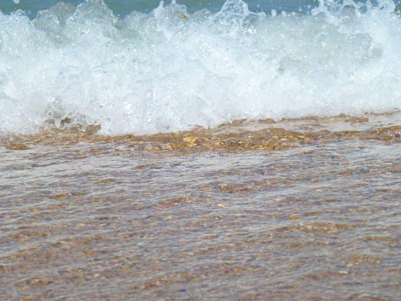 Rolamento espumoso da onda na praia imagens de stock