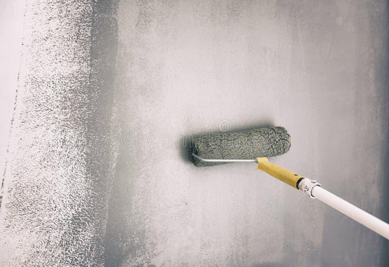 Rolborstel het Schilderen op Muur Arbeider het Schilderen op Muur met Gray Paint royalty-vrije stock foto