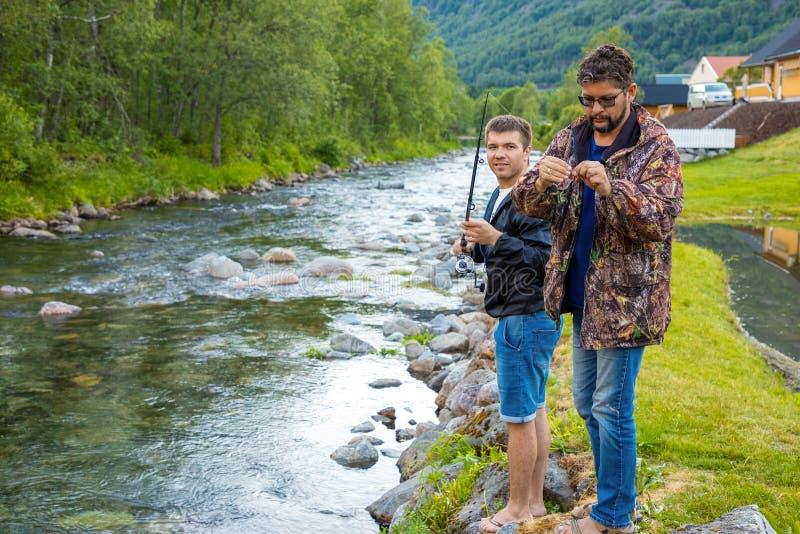 Roldal Norge - 26 06 2018: Fadern och sonen är fishermans flyger fiske i floden nära den Rodal staden, Norge arkivbilder