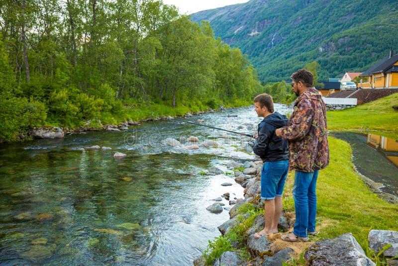 Roldal, Noruega - 26 06 2018: El padre y el hijo son pesca con mosca de los fishermans en el río cerca de ciudad de Rodal, Norueg imagen de archivo libre de regalías