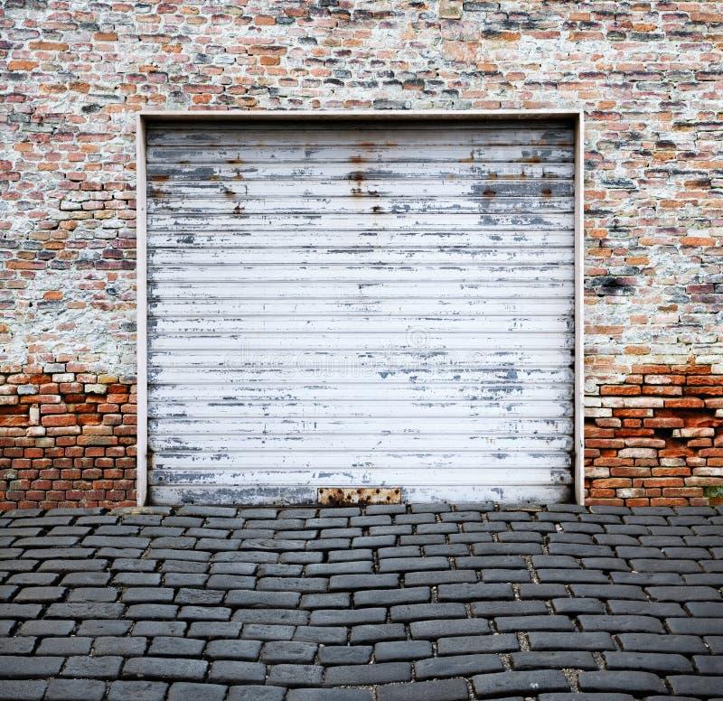 Role acima a porta da garagem na parede de tijolo foto de stock