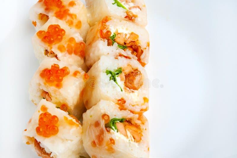Role o papel de arroz, os salmões do teriyaki, a salada e o caviar dos salmões foto de stock royalty free