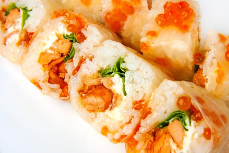 Role o papel de arroz, os salmões do teriyaki, a salada e o caviar dos salmões foto de stock