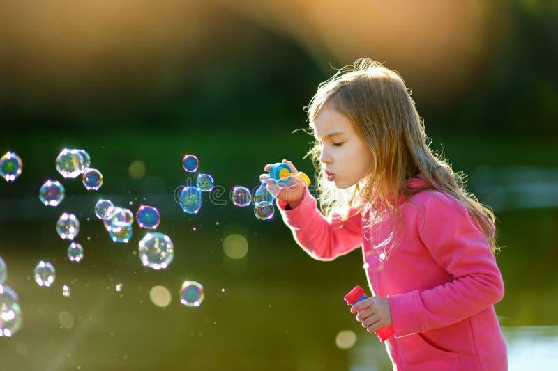 Rolig älskvärd liten flicka som blåser såpbubblor royaltyfria bilder