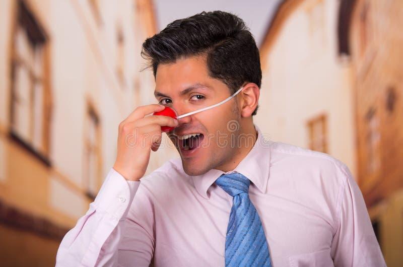 Rolig affärsman med den röda plast- näsan royaltyfri foto