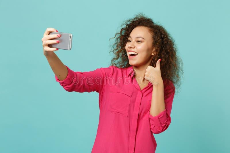 Rolig afrikansk flicka i tillfällig kläder som visar tummen upp att göra selfie som skjutas på mobiltelefonen som isoleras på blå royaltyfria foton