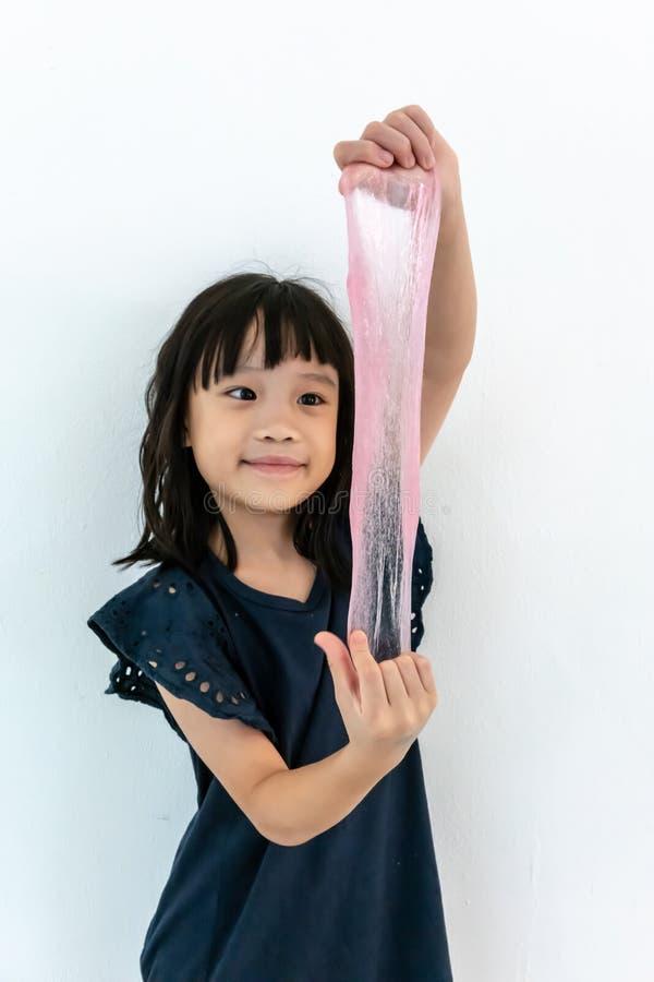 Rolig asiatisk flicka som spelar med rosa slam barndom fritidbegrepp arkivbilder
