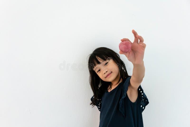 Rolig asiatisk flicka som spelar med rosa slam barndom fritidbegrepp royaltyfri fotografi