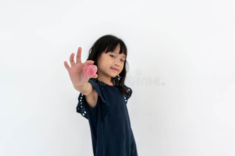 Rolig asiatisk flicka som spelar med rosa slam barndom fritidbegrepp arkivfoto