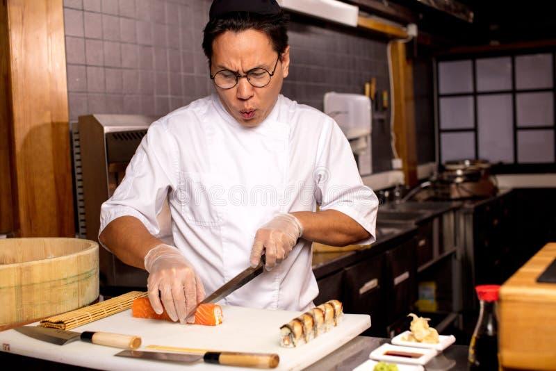 Rolig asiatisk kock som sjunger sånger, medan förbereda sushi arkivbild